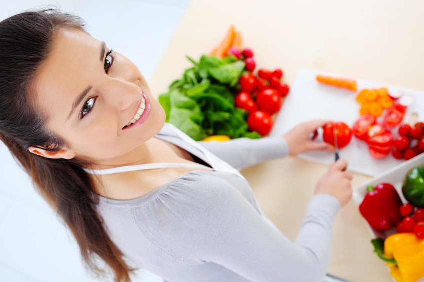 Young woman in her kitchen cutting ingredients.